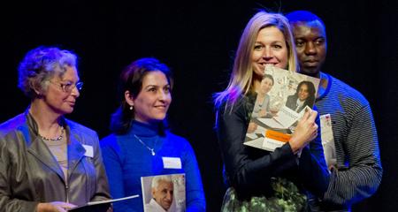 Prinses Maxima neemt het eerst exemplaar van de speciale publicatie Taal voor Twee in ontvangst.